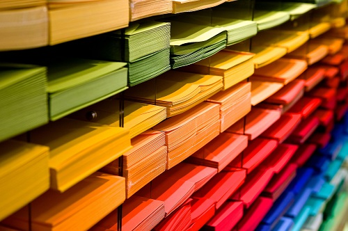 Series of paper trays containing different coloured paper. Each colour is arranged horizontally forming a rainbow like pattern.