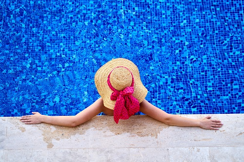 Lady wearing sun hat looking out into a calm swimming pool taken from above