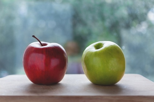 A red apple sits next to a green apple on a wooden block in front of an out of focus window