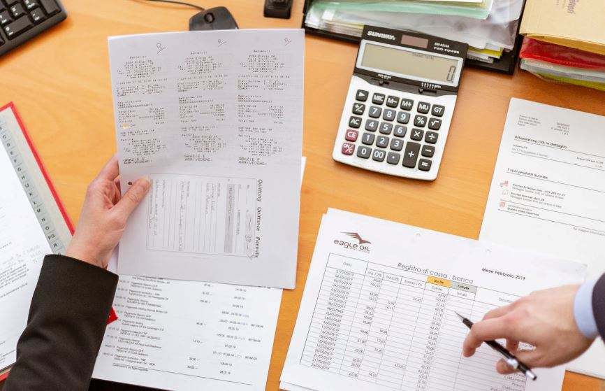 Invoices, statements and a calculator sit on a busy desk as two colleagues confer