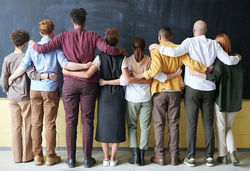 Rear view of line up of people with arms over each other's shoulders facing a blackboard