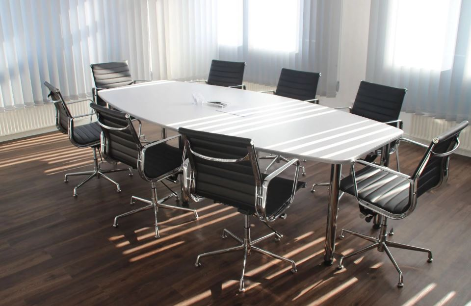 Empty conference room with white table, black chairs and sunlight piercing closed blinds