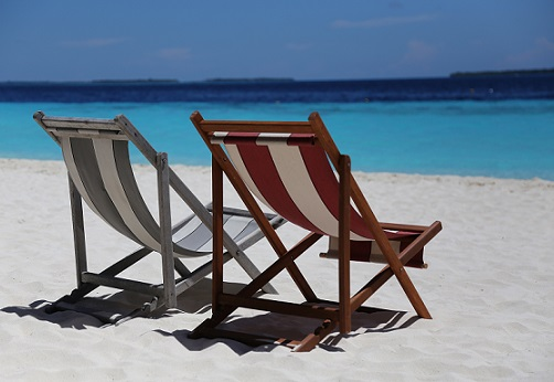 One red and white striped deck chair sits next to a grey and white striped deck chair on a white sand beach in front of a turquoise ocean fading to navy in the distance