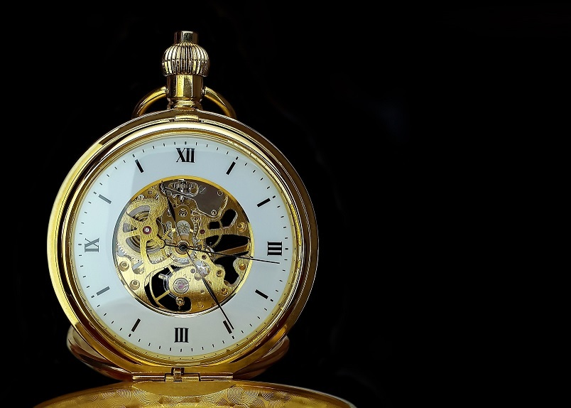 Golden pocket watch with white face and visible mechanism offset against a black background