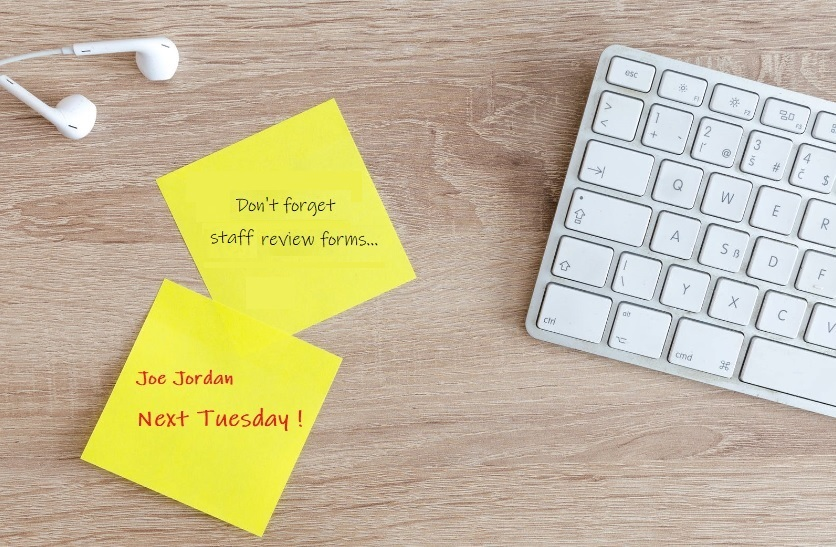 Light coloured wooden desk with earphones and apple keyboard, two yellow post notes with reminders