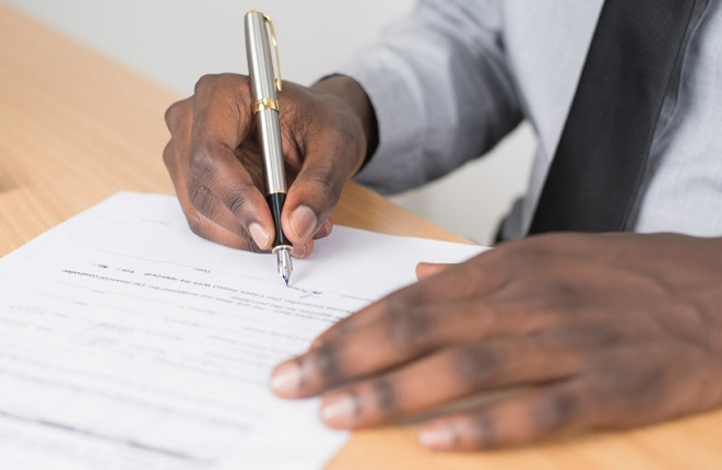 Employee with shirt and tie signs paperwork with a fountain pen at a wooden desk