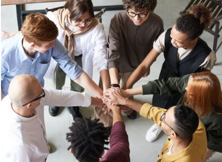Group of people touching hands in a circle