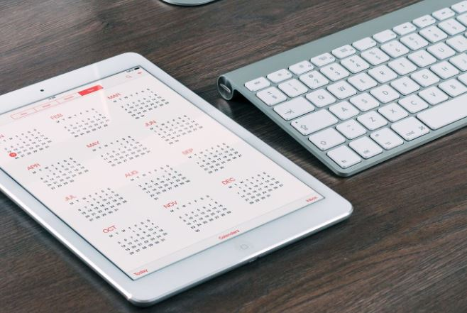 Modern Keyboard and tablet displaying a calendar placed on a dark wood desk