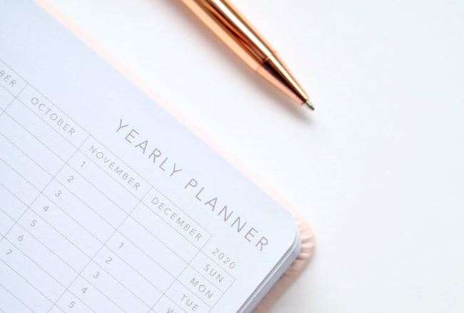 Gold pen and year planner open on a white background